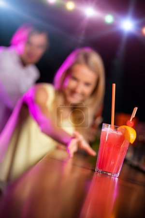 Photo pour Belle fille blonde avec cocktail assis au comptoir du bar - image libre de droit