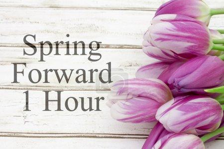 Photo pour Changement d'heure printanière, Quelques tulipes avec bois altéré et texte Printemps vers l'avant 1 heure - image libre de droit
