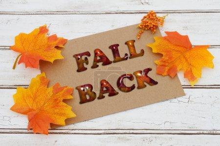 Photo pour Fall Back Card, Une carte brune avec des mots Fall Back sur un fond de bois en détresse avec feuilles d'automne - image libre de droit