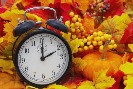 Photo pour Changement d'heure d'automne, feuilles d'automne et réveil avec une citrouille - image libre de droit