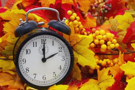 Photo pour Changement d'heure d'automne, feuilles d'automne et réveil - image libre de droit