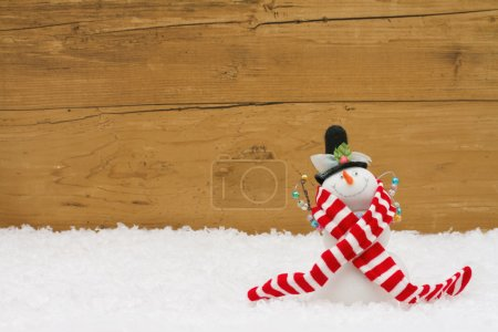 Photo for Happy Holidays, A Snowman on snow with a weathered wood background and copy-space for your message - Royalty Free Image