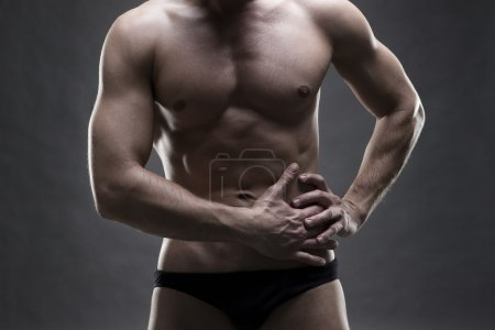 Pain in the left side of the muscular male body. Handsome bodybuilder posing on gray background. Low key close up studio shot
