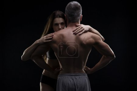 Young adult muscular man and woman. Sexy couple on black background