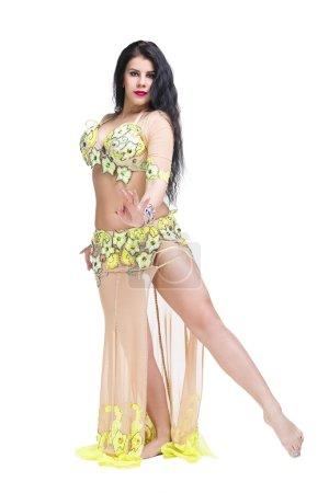 Photo pour Jeune belle femme orientale exotique exécute la danse du ventre en robe ethnique. Isolé sur fond blanc. Studio shot - image libre de droit