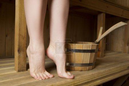Photo pour Belles jambes féminines dans le sauna, accessoires de bain. seau en bois - image libre de droit