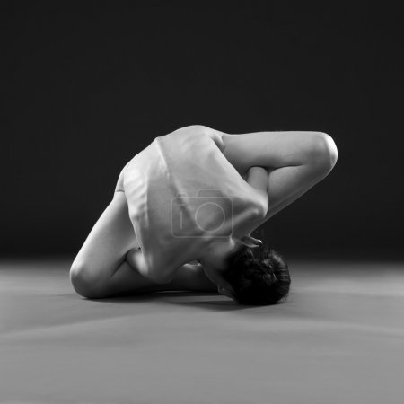 Naked yoga. Beautiful sexy body of young woman on gray background