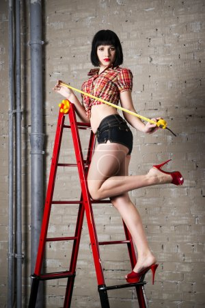 Beautiful young sexy woman in red high heels posing with construction equipment