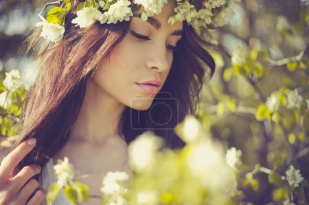 Romantic lady in a wreath of apple trees