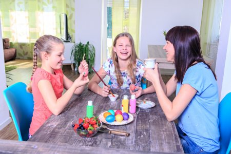 Photo for Mother with daughters preparing eggs for Easter at home - Royalty Free Image