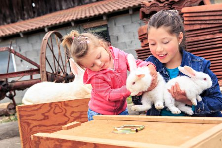 Photo pour Petites filles avec un lapin devant la ferme - image libre de droit