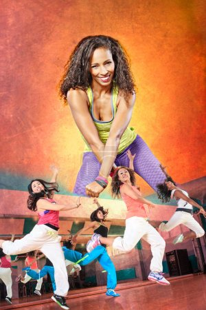 Young woman at fitness exercise or zumba dancing...