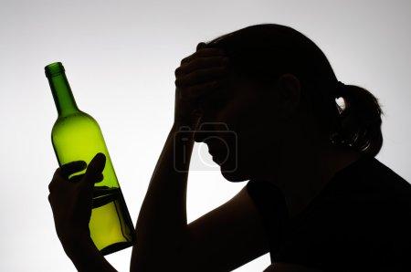 Photo pour Silhouette de femme alcoolique avec une bouteille de vin - image libre de droit