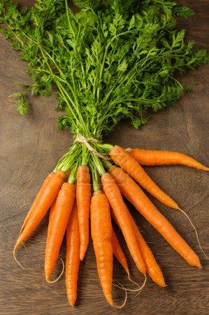 Photo pour Un tas de carottes fraîches sur la table en bois - image libre de droit