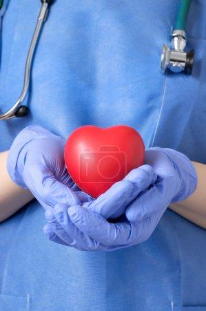 Photo pour Femme médecin tenant une forme coeur rouge - image libre de droit