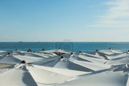 Photo pour Ambiance vacances en été, journée ensoleillée en été et parasols blancs à Nice, France. Parapluies blancs sur une plage en fond bleu ciel clair. Photo de haute qualité - image libre de droit
