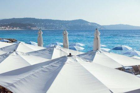 Photo pour Journée ensoleillée d'été et parasols blancs à Nice, France. Ambiance de vacances en été sur la Côte d'Azur. Parapluies blancs sur une plage au ciel bleu clair et montagnes en arrière-plan. Photo de haute qualité - image libre de droit
