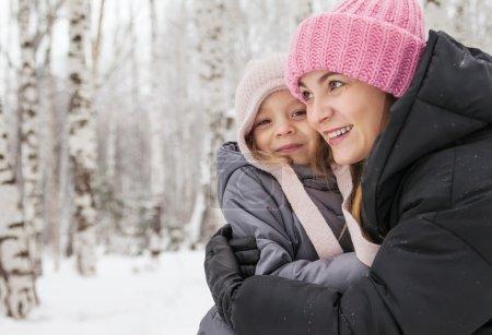 Photo pour Bonne mère et fille marchant dans une forêt de bouleaux en hiver - image libre de droit