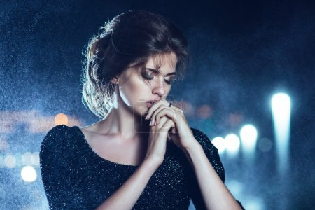 Photo pour Belle femme en robe noire, posant sur un fond de lumières de ville - image libre de droit