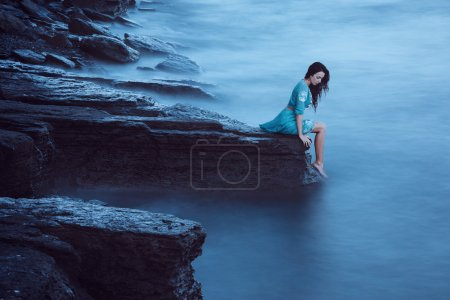 Photo for Beautiful young woman on sea in twilight. Long time exposure - Royalty Free Image