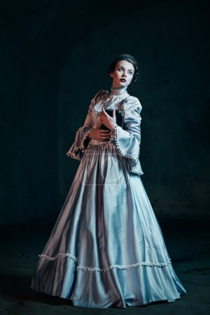 Photo for Woman in victorian dress imprisoned in a dungeon - Royalty Free Image