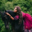 Beautiful gypsy in violet dress with a black horse...
