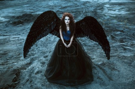 Photo for Pretty girl-demon with black wings behind her back - Royalty Free Image