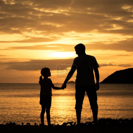 Photo for Father and daughter standing on the beach at the sunset time. - Royalty Free Image
