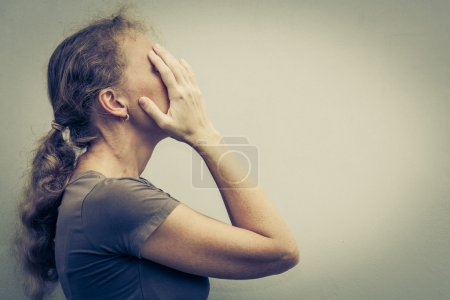 Photo for Portrait of one sad woman standing near a wall and holding her head in her hands - Royalty Free Image
