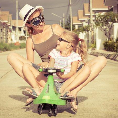 Photo pour Mère et fille jouant près d'une maison à l'heure de la journée. concept de famille conviviale. - image libre de droit