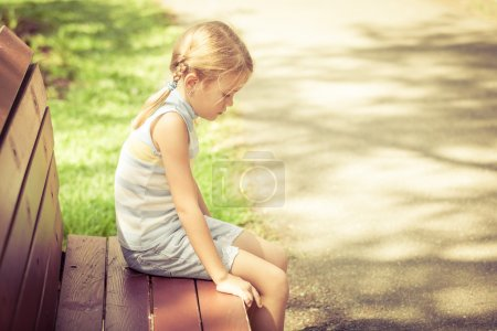 Sad little girl sitting on bench in the park at the day time