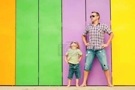Photo pour Father and son playing near the house at the day time. They standing near are the colorful wall. Concept of friendly family. - image libre de droit
