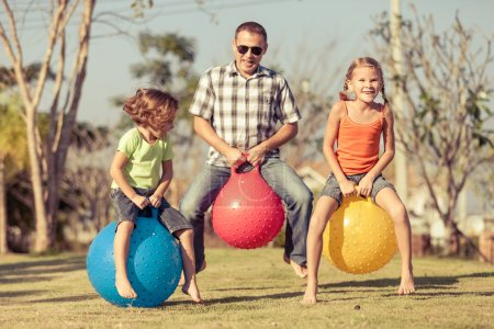 Photo for Dad and children playing on the lawn in front of house at the day time - Royalty Free Image
