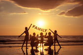 "Постер, картина, фотообои ""Happy family standing on the beach at the sunset time. """