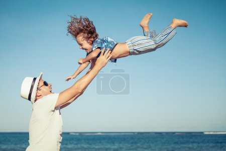 Father and son playing on the beach at the day time.
