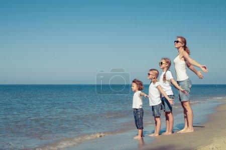 Matka i dzieci bawiące się na plaży w czasie dnia.
