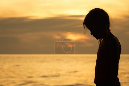 Photo for Portrait of sad blond little girl standing on the beach at sunset time. - Royalty Free Image