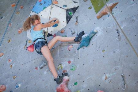 teenager climbing a rock wall
