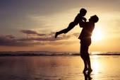 Otec a syn hraje na pláži při západu slunce