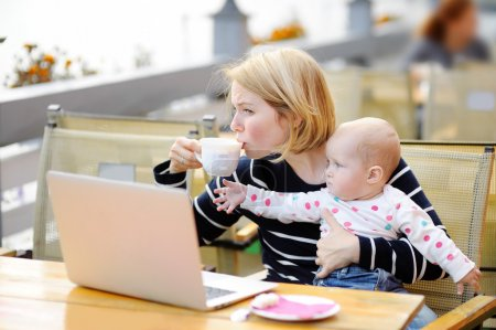 Photo for Tired young mother working oh her laptop, holding daughter and drinking coffee - Royalty Free Image