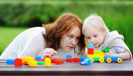 Woman with his son playing with colorful plastic blocks