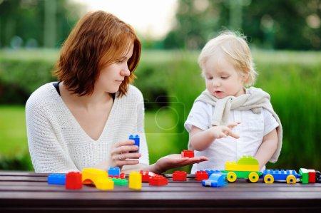 Photo pour Jeune femme avec son fils tout-petits jouer avec des blocs en plastique colorés - image libre de droit