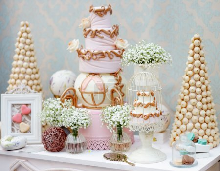 Photo for Elegant sweet table with big cake and macaroon on dinner or event party - Royalty Free Image