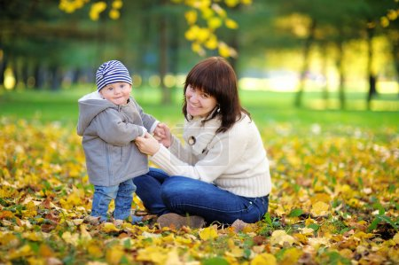 Young mother with her baby boy in the autumn park