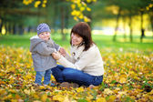Giovane madre con il suo bambino nel parco dautunno
