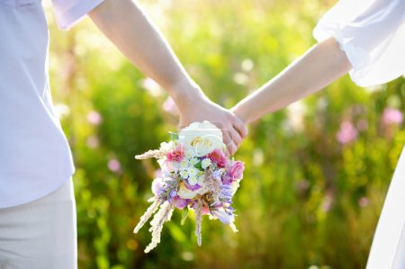 Young couple holding wild flowers bouquet