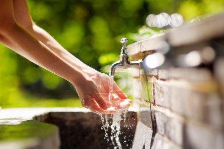 Woman washing hands in a city fountain