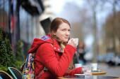 Frau trinkt Kaffee in einem Straßencafé