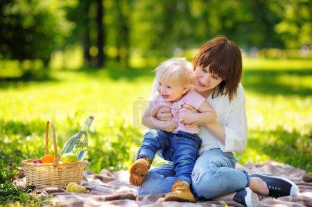 Photo pour Belle jeune femme et son adorable petit garçon ayant un pique-nique dans le parc ensoleillé - image libre de droit