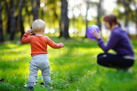 Photo pour Garçon enfant en bas âge avec sa jeune mère jouant avec ballon au parc ensoleillé - image libre de droit